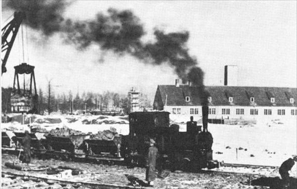 二號火葬場前的火車照片,圖片右方的小幢建築物為二號火葬場,可隱約看見注入毒氣的煙囪。